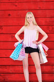 Composite image of pretty young blonde holding shopping bags Stock Photos