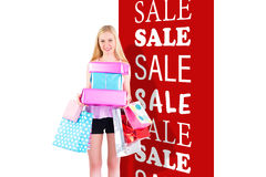 Composite image of pretty young blonde holding shopping bags Stock Photography