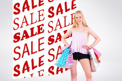 Composite image of pretty young blonde holding shopping bags Stock Image