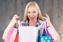 Composite image of pretty young blonde holding shopping bags Royalty Free Stock Image