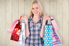 Composite image of pretty young blonde holding shopping bags Royalty Free Stock Images