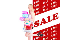 Composite image of pretty young blonde holding shopping bags and gifts Royalty Free Stock Image