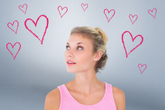 Composite image of pretty young blonde in pink looking up Royalty Free Stock Photos