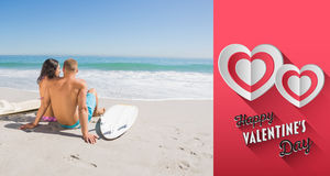 Composite image of pretty young couple with their surfboards looking at the sea Stock Photography