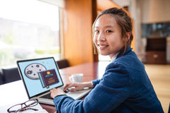 Composite image of print. Print against portrait of young woman using laptop Stock Photo