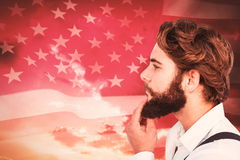 Composite image of profile view of hipster touching beard Stock Photo