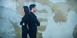 Composite image of profile view of sad couple standing back to back. Profile view of sad couple standing back to back against rusty weathered wall Royalty Free Stock Photos