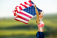 Composite image of profile view of sportswoman raising an american flag. Profile view of sportswoman raising an american flag  against scenic landscape Stock Image