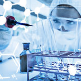 Composite image of protected female scientist dropping blue liquid in a test tube Stock Images