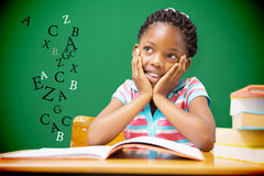 Composite image of pupil sitting at her desk Royalty Free Stock Image