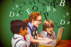 Composite image of pupils using laptop Royalty Free Stock Photo