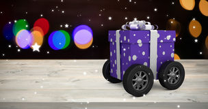 Composite image of purple wrapped with polka dot gift box on wheels Stock Images