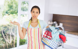 Composite image of puzzled young woman holding laundry basket full of dirty laundry Royalty Free Stock Photos