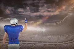 Composite image of rear view of american football player pointing Royalty Free Stock Photo