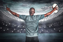 Composite image of rear view of athlete with arms raised holding rugby ball Royalty Free Stock Photography