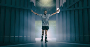 Composite image of rear view of athlete with arms raised holding rugby ball 3d Royalty Free Stock Photography