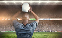 Composite image of rear view of athlete throwing rugby ball Stock Images