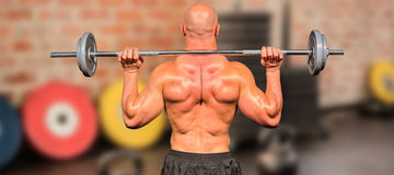 Composite image of rear view of bodybuilder lifting crossfit stock images