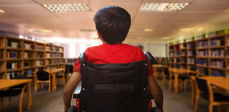 Composite image of rear view of boy sitting in wheelchair Royalty Free Stock Images