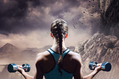 Composite image of rear view of braided hair woman lifting dumbbells Royalty Free Stock Photo