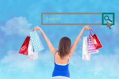 Composite image of rear view of a brunette woman raising shopping bags Royalty Free Stock Photography