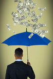 Composite image of rear view of businessman carrying blue umbrella Royalty Free Stock Photography