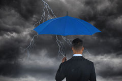 Composite image of rear view of businessman carrying blue umbrella Royalty Free Stock Images