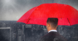 Composite image of rear view of businessman carrying red umbrella Stock Images