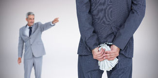 Composite image of rear view of businessman with handcuff and banknotes Royalty Free Stock Photo