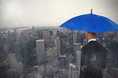 Composite image of rear view of businessman holding blue umbrella and briefcase. Rear view of businessman holding blue umbrella and briefcase against new york Stock Image