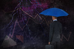 Composite image of rear view of businessman holding blue umbrella and briefcase. Rear view of businessman holding blue umbrella and briefcase against starry Royalty Free Stock Photos