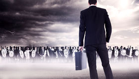 Composite image of rear view of businessman holding a briefcase Royalty Free Stock Photos