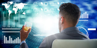 Composite image of rear view of businessman holding whisky glass. Rear view of businessman holding whisky glass against spiral of shiny binary code Stock Photography