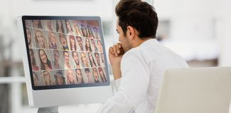 Composite image of rear view of businessman looking at computer monitor stock photos