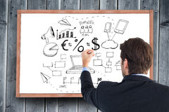 Composite image of rear view of businessman writing with a white chalk Stock Photos