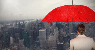 Composite image of rear view of businesswoman carrying red umbrella Stock Image