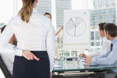 Composite image of rear view of businesswoman with fingers crossed over white background stock photos