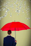 Composite image of rear view of businesswoman holding red umbrella. Rear view of businesswoman holding red umbrella against light green background Royalty Free Stock Photo