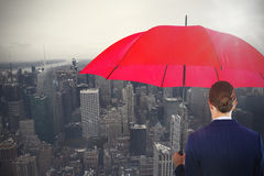 Composite image of rear view of businesswoman holding red umbrella Stock Photo