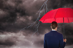 Composite image of rear view of businesswoman holding red umbrella. Rear view of businesswoman holding red umbrella against stormy sky Stock Image