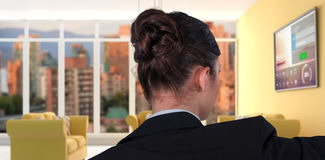 Composite image of rear view of businesswoman using digital screen. Rear view of businesswoman using digital screen against computer generated interior of modern Stock Image