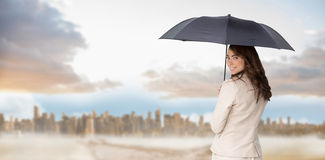 Composite image of rear view of classy businesswoman holding umbrella Stock Photography