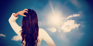 Composite image of rear view of confused woman with hand in hair. Rear view of confused woman with hand in hair  against cloudy sky with sunshine Stock Photos