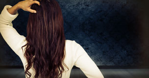 Composite image of rear view of confused woman with hand in hair. Rear view of confused woman with hand in hair  against dark grimy room Stock Photos