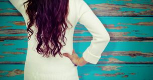 Composite image of rear view of confused woman with hand in hair. Rear view of confused woman with hand in hair  against horizontal wood panelling Royalty Free Stock Photos