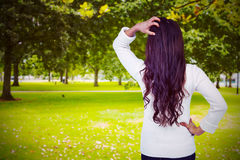 Composite image of rear view of confused woman with hand in hair. Rear view of confused woman with hand in hair  against park Stock Image
