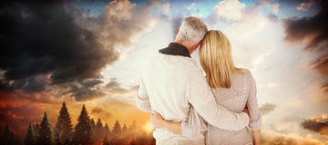 Composite image of rear view of couple with arms around Royalty Free Stock Photography
