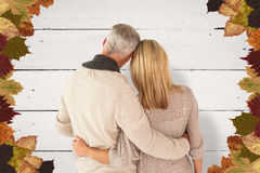 Composite image of rear view of couple with arms around Royalty Free Stock Photos