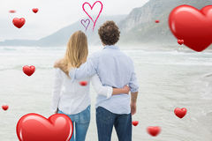 Composite image of rear view of a couple looking at sea Stock Images