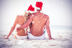Composite image of rear view of couple with santa hat sitting together at beach Royalty Free Stock Image